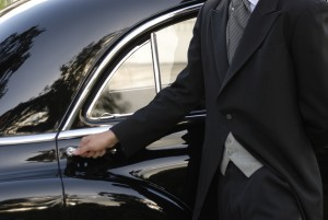 Close up photo of a chauffeur hand dressed with a frock coat, opening an antique cas«s door.